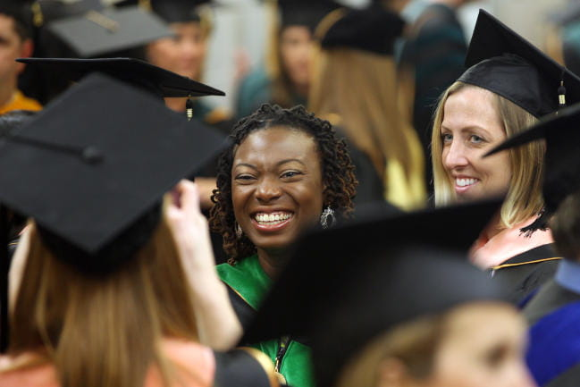 Students in academic regalia smiling during commencement ceremony
