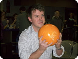 Image of a resident holding an orange bowling ball.