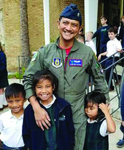 Photograph of Dr. Alec DeCastro with his children at a Veterans Day celebration at their school.