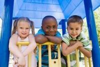 Three children smiling leaning over the top of a climbing structure on a playground