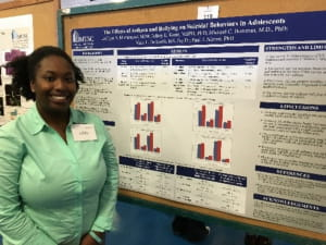 Ph.D. student standing beside research poster at Student Research Day