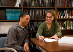 Smiling female professor points to biostatistical equation on a piece of paper with male MPH student