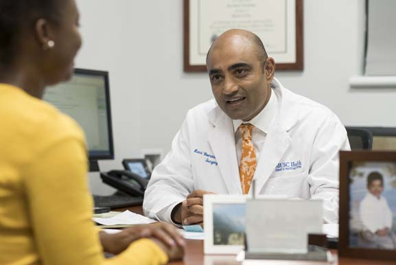 Dr. Ravi Veeraswamy meeting with a member of his staff in his office.