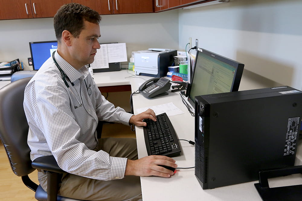 Doctor Meissner sitting at computer, looking at the screen